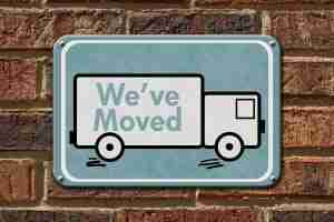 We have Moved Sign,  A blue sign with the word We've Moved with a truck on a brick wall