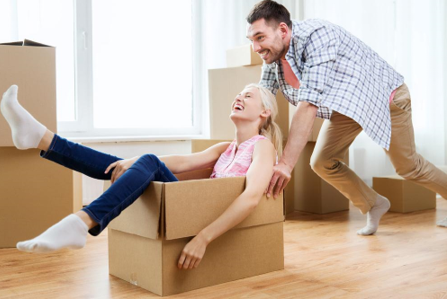 couple moving boxes having fun