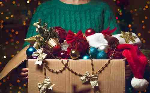 woman holding christmas decorations box
